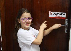 """A aluna Valentina Ammari da Cruz, do 3º ano entra na sala de aula: Todos os objetos da escola estão identificados com seu correspondente em inglês. Na maçaneta, vê-se a inscrição """"Doorknob""""."""