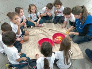 """A professora Maria Alice Dantas Farinha Boveto corta uma laranja para os alunos: """"até alguns legumes eles já provaram""""."""